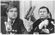 Senator Frank Church showing a poison dart gun.