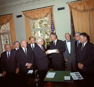 The Warren Commissioners deliver their report to President Johnson.