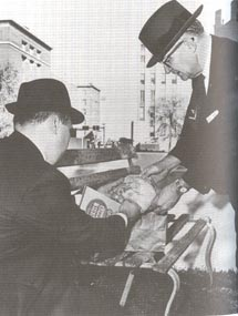 Figure 26. Press photo of bench with lunch bags being examined by two plainclothes officers