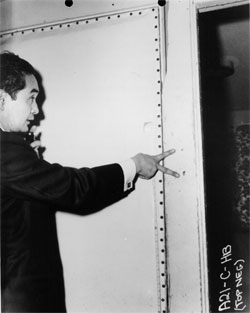 Photograph of Los Angeles Coroner Thomas Noguchi pointing to two bullet holes in doorfram
